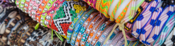 Colorful handmade bracelets made of beads and thread on the counter of gift shop